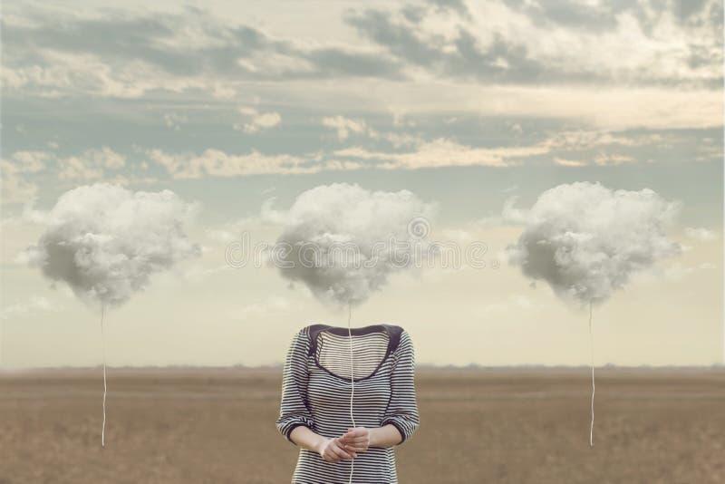 La donna sceglie la sua nuvola per nascondere il suo fronte fotografia stock
