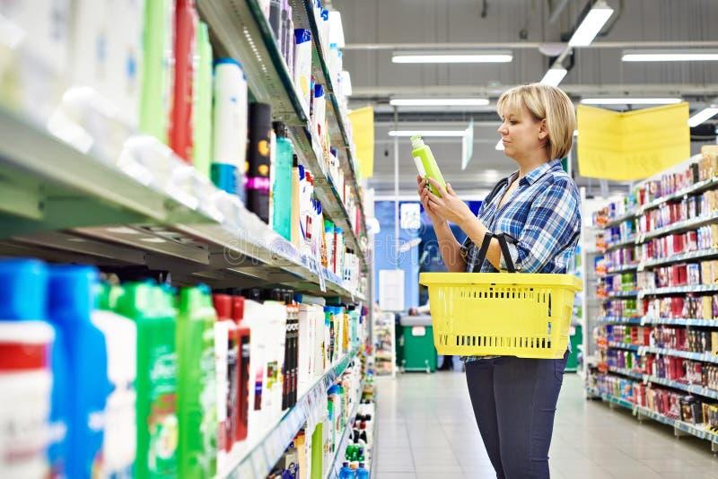 La donna sceglie lo sciampo nel dipartimento dei cosmetici immagini stock libere da diritti
