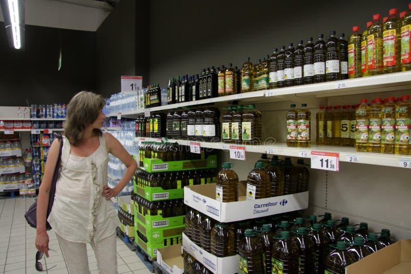 La donna sconosciuta sceglie l'olio d'oliva in deposito immagini stock libere da diritti