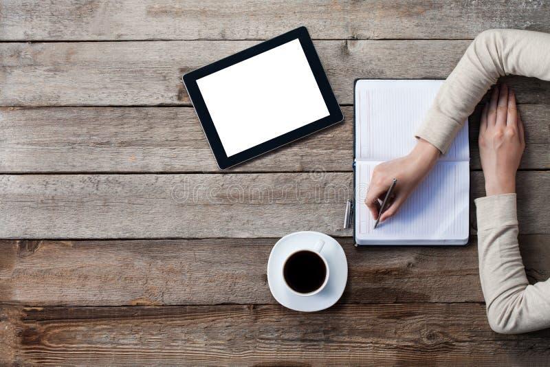 La donna scrive su una carta con lo schermo della compressa digitale accanto lei fotografie stock libere da diritti