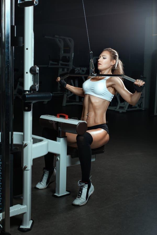 La donna scuote i suoi muscoli sul simulatore nella palestra fotografie stock