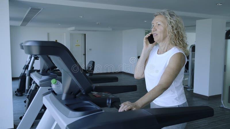 La donna senior è impegnata su una pedana mobile nella palestra conversazione femminile sul telefono che fa la pedana mobile fotografie stock libere da diritti
