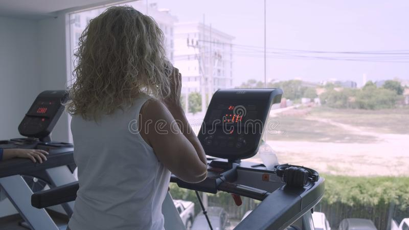 La donna senior è impegnata su una pedana mobile nella palestra conversazione femminile sul telefono che fa la pedana mobile fotografie stock