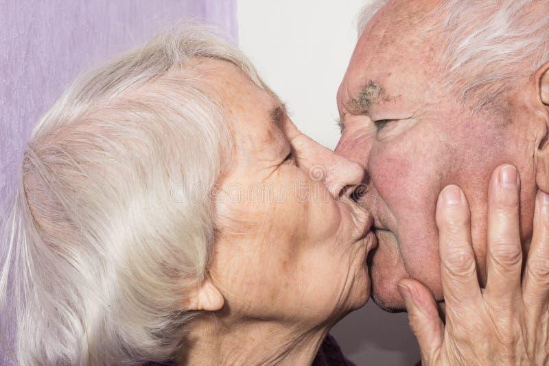 La donna senior che bacia uomo anziano fotografia stock