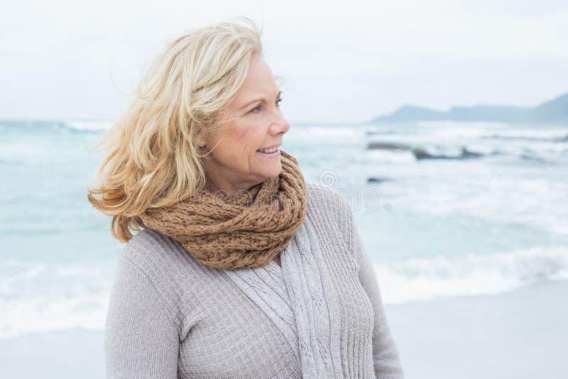 La donna senior contemplativa distoglie lo sguardo la spiaggia fotografie stock libere da diritti