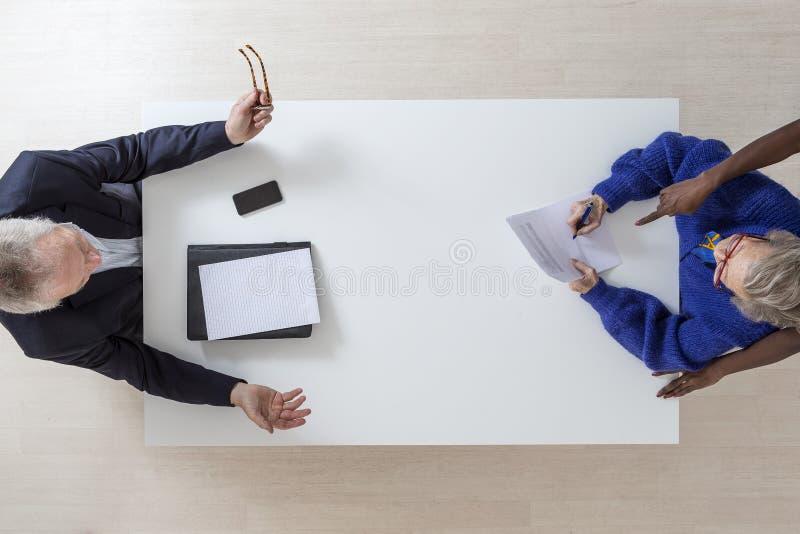 La donna senior firma la disposizione per la sua morte e, documento del testamento di eredità in un ufficio di notaio dell'avvoca fotografia stock libera da diritti