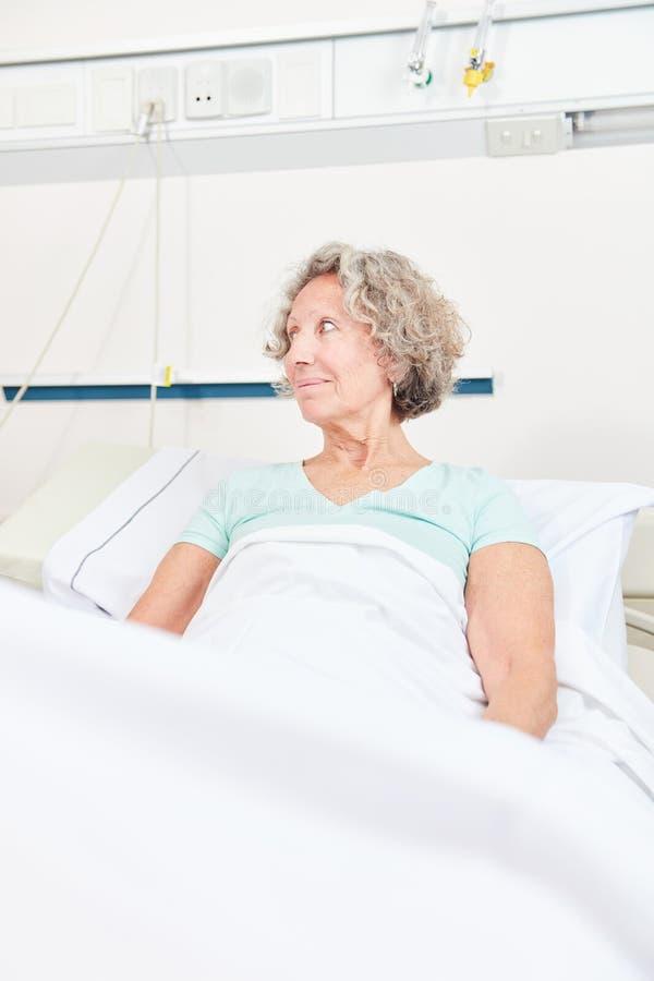 La donna senior malata sta trovandosi a letto fotografie stock