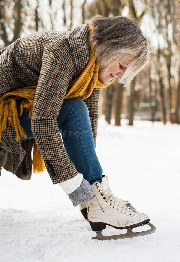 La donna senior nell'inverno copre mettere sui vecchi pattini da ghiaccio immagini stock