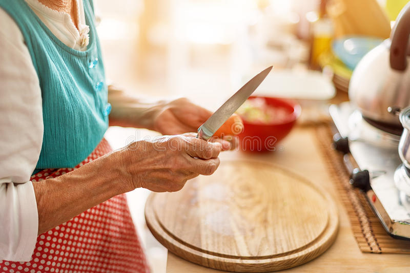 La donna senior passa lo spezzettamento delle verdure a pezzi su un bordo di legno nella cucina fotografie stock libere da diritti