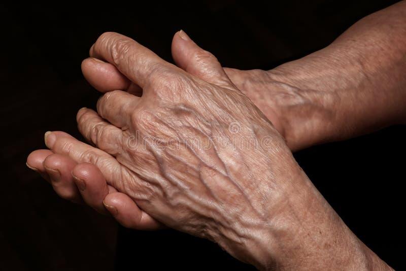 La donna senior piegata ha corrugato le mani vicino su La vecchiaia, invecchia proble immagine stock libera da diritti