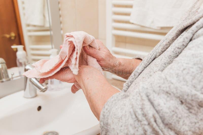 La donna senior pulisce le sue mani con un asciugamano in bagno a tempo la mattina, primo piano fotografie stock libere da diritti