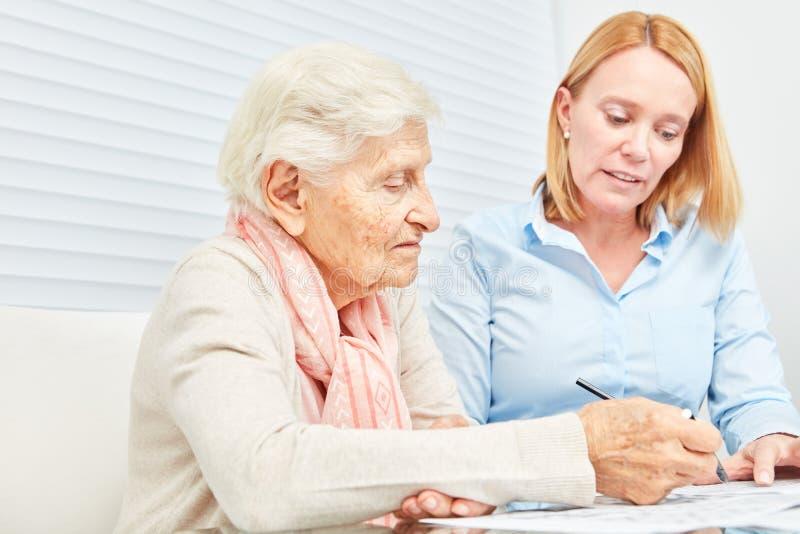 La donna senior risolve i puzzle come addestramento di memoria fotografia stock