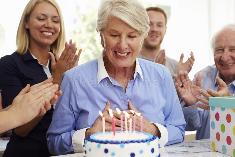 La donna senior spegne le candele della torta di compleanno alla festa di famiglia immagini stock