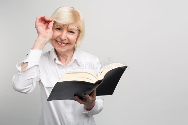 La donna senior sta stando nella stanza e sta leggendo un libro Sta provando ad imparare il somethinf nuovo al pensionamento perc fotografia stock