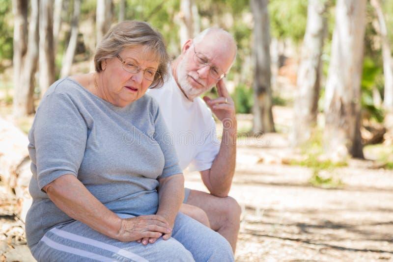 La donna senior turbata si siede con il marito interessato all'aperto immagini stock