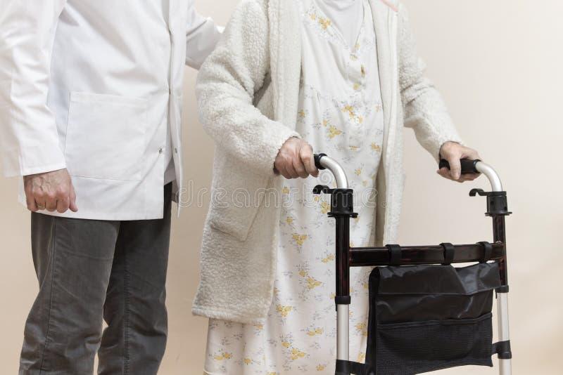 La donna senior in un accappatoio ed in una camicia da notte bianchi va con un camminatore di riabilitazione L'infermiere sostien fotografie stock libere da diritti