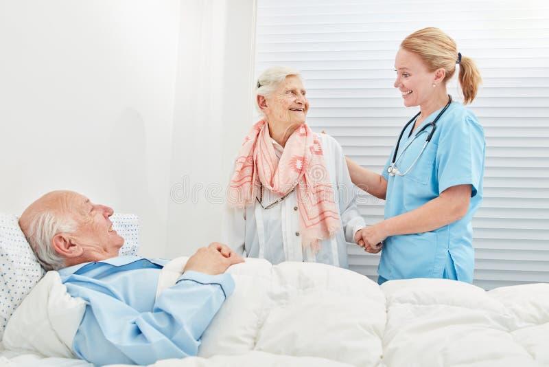 La donna senior visita il suo marito nell'ospedale immagini stock