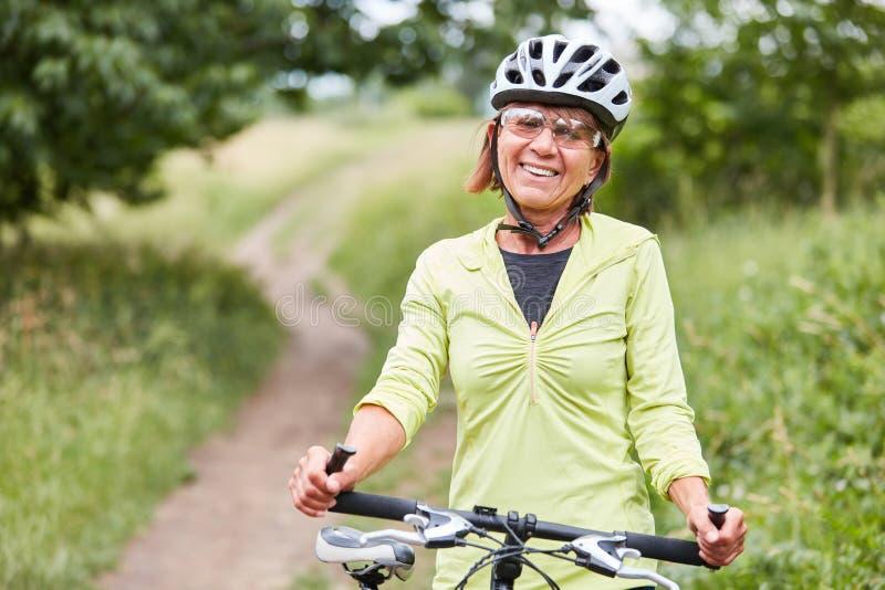 La donna senior vitale ? su un giro della bici fotografia stock libera da diritti