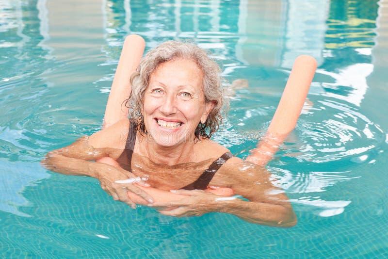 La donna senior vitale sta imparando nuotare fotografia stock libera da diritti