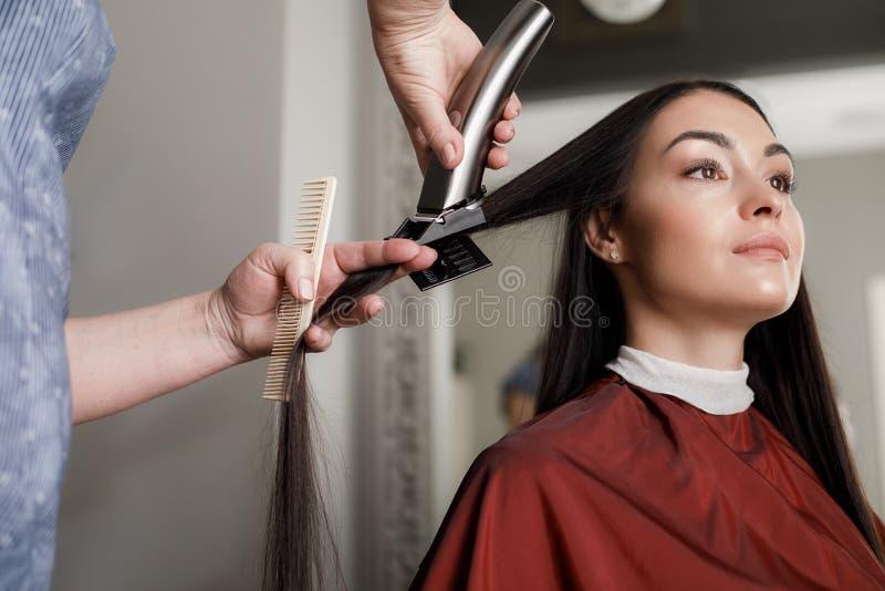 La donna serena sta facendo laminare i capelli dal professionista immagine stock libera da diritti