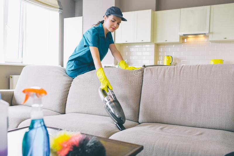La donna seria sta e pende al sofà Lavora con il piccolo aspirapolvere La ragazza indossa l'uniforme ed i guanti fotografia stock