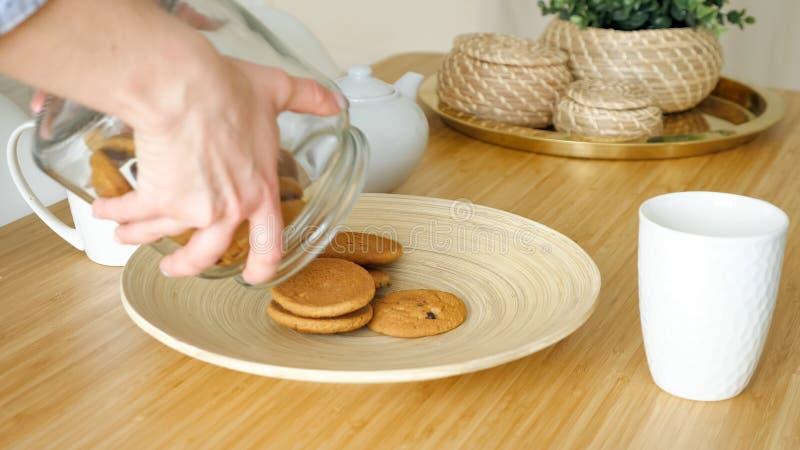 La donna serve la prima colazione con i biscotti sulla tavola in cucina fotografia stock