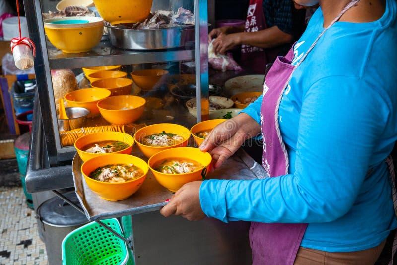 La donna serve sulla minestra di pollo per i clienti su una corte di alimento di Ipoh fotografia stock