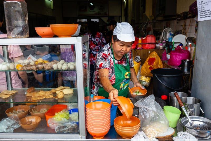 La donna serve sulle tagliatelle per i clienti su una corte di alimento di Ipoh fotografia stock