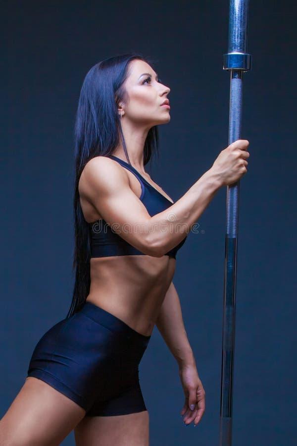 La donna sexy atletica brutale tiene un bilanciere Il concetto dell'esercizio mette in mostra, annunciando una palestra isolato s immagine stock libera da diritti