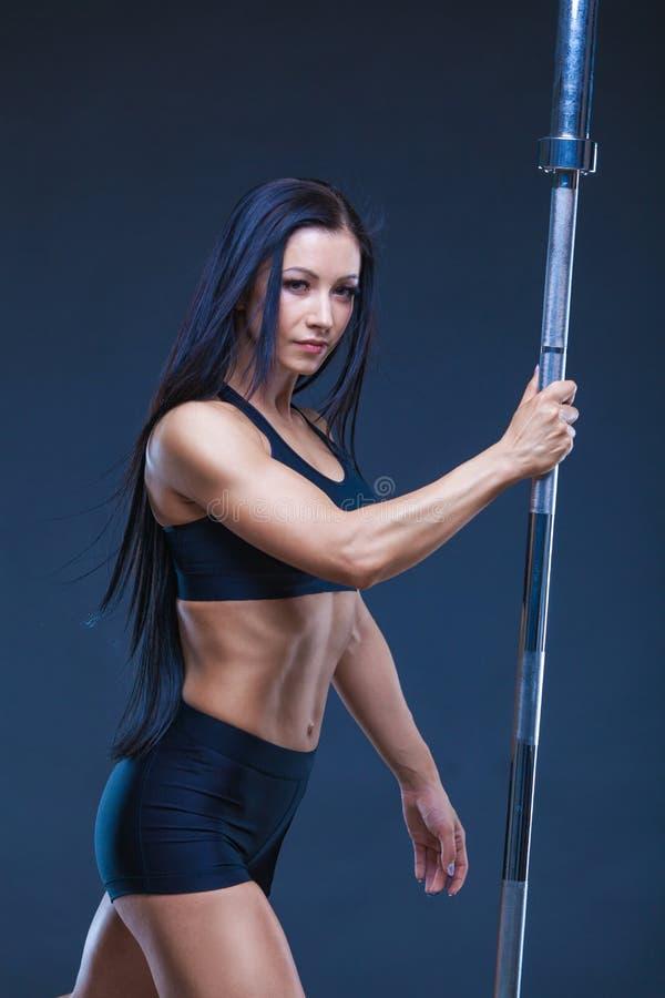 La donna sexy atletica brutale tiene un bilanciere Il concetto dell'esercizio mette in mostra, annunciando una palestra isolato s immagini stock libere da diritti