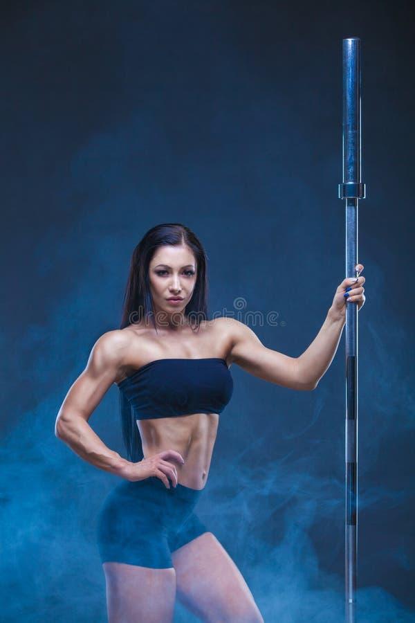 La donna sexy atletica brutale tiene un bilanciere Il concetto dell'esercizio mette in mostra, annunciando una palestra isolato s immagini stock