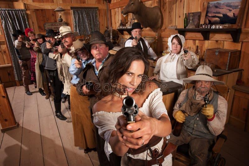 La donna sexy indica la pistola in salone fotografia stock