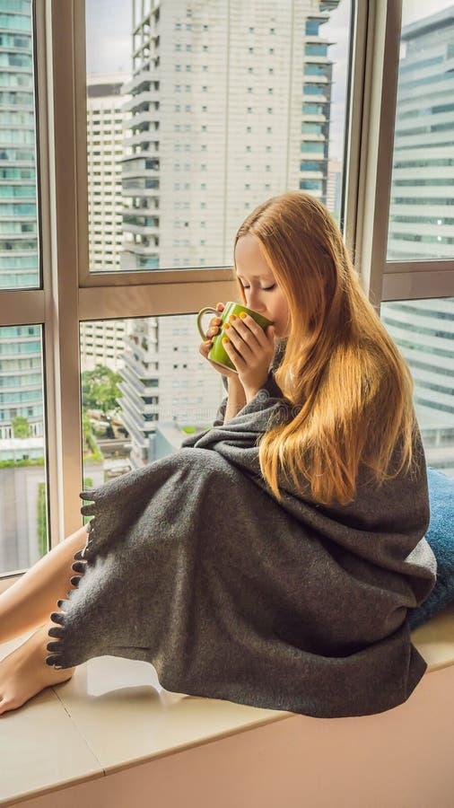 La donna si è avvolta in una coperta e nell'esame del FORMATO VERTICALE grande della città per la storia di Instagram o la dimens fotografie stock libere da diritti