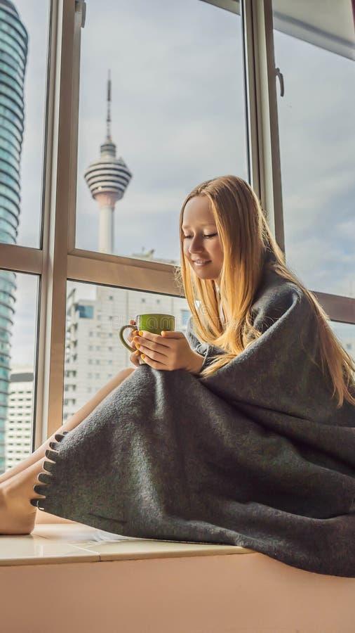 La donna si è avvolta in una coperta e nell'esame del FORMATO VERTICALE grande della città per la storia di Instagram o la dimens immagini stock