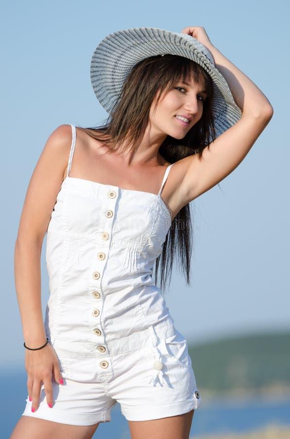 La donna si è vestita con i pagliaccetti bianchi delle tute che joying il giorno soleggiato immagine stock