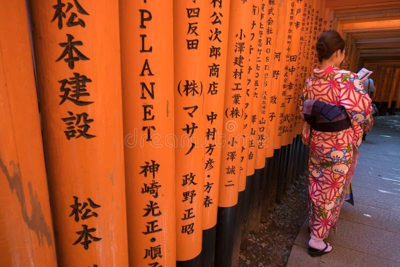 La donna si è vestita in costume giapponese tradizionale che cammina sotto i tori fotografie stock libere da diritti