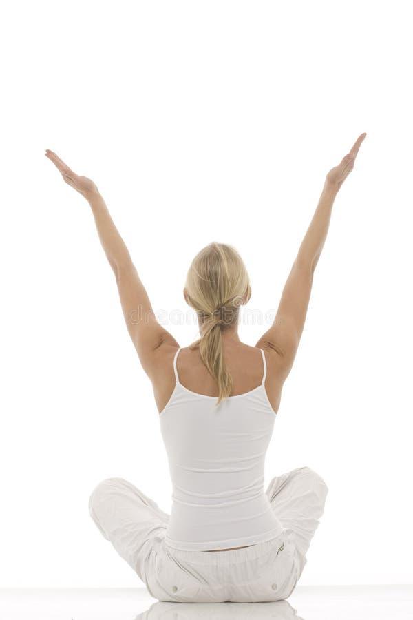 La donna si è vestita nel bianco che si siede a gambe accavallate fare immagini stock libere da diritti