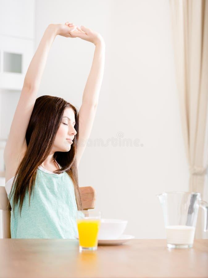 La donna si allunga che si siede al tavolo da cucina fotografia stock libera da diritti