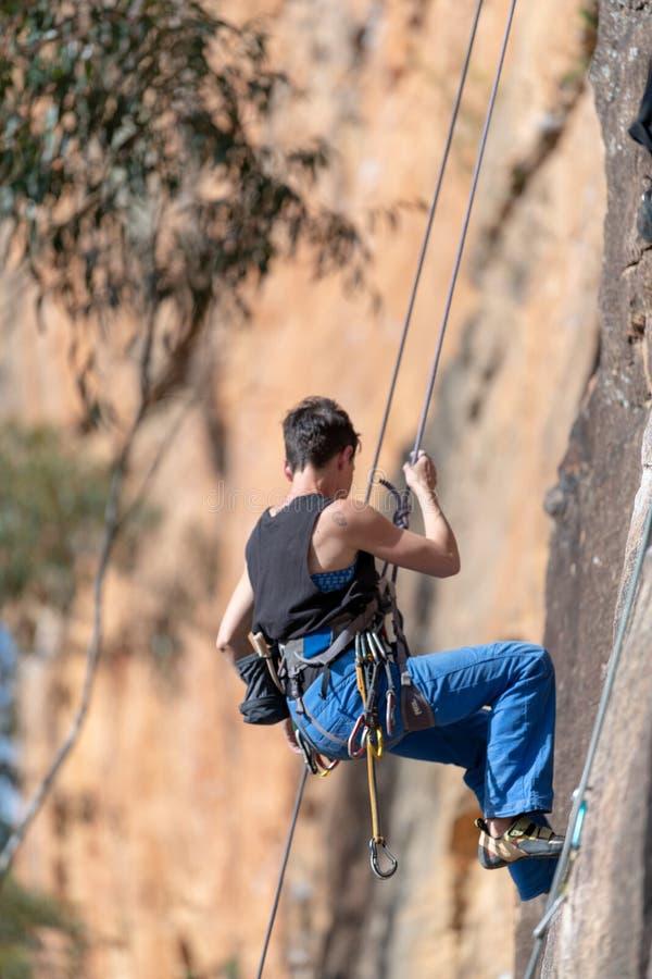 La donna si cala in corda doppia giù il fronte verticale della scogliera al circuito di Ledge Porters Pass Centennial Glen delle  immagini stock libere da diritti