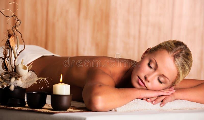 La donna si distende nel salone della stazione termale fotografia stock