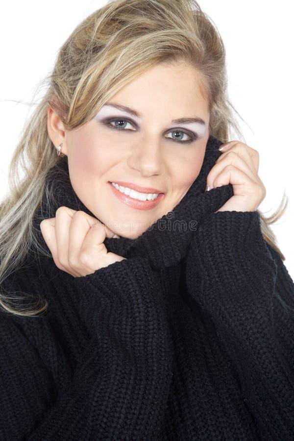 La donna si rannicchia su in maglioni fotografia stock libera da diritti
