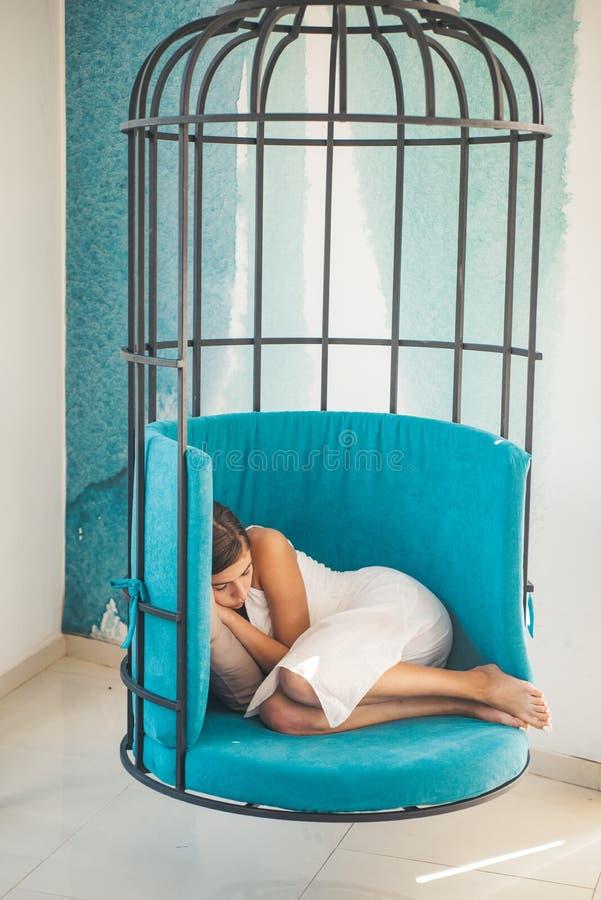 La donna si rilassa nella sedia della gabbia a casa sonno di giorno della ragazza stanca nella sedia della gabbia dolce e sogno d fotografie stock libere da diritti