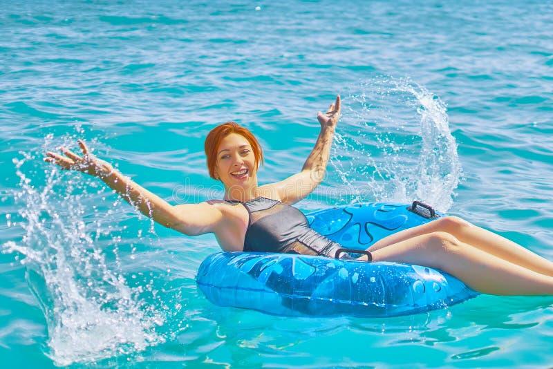 La donna si rilassa sull'anello gonfiabile in acqua di mare immagini stock libere da diritti