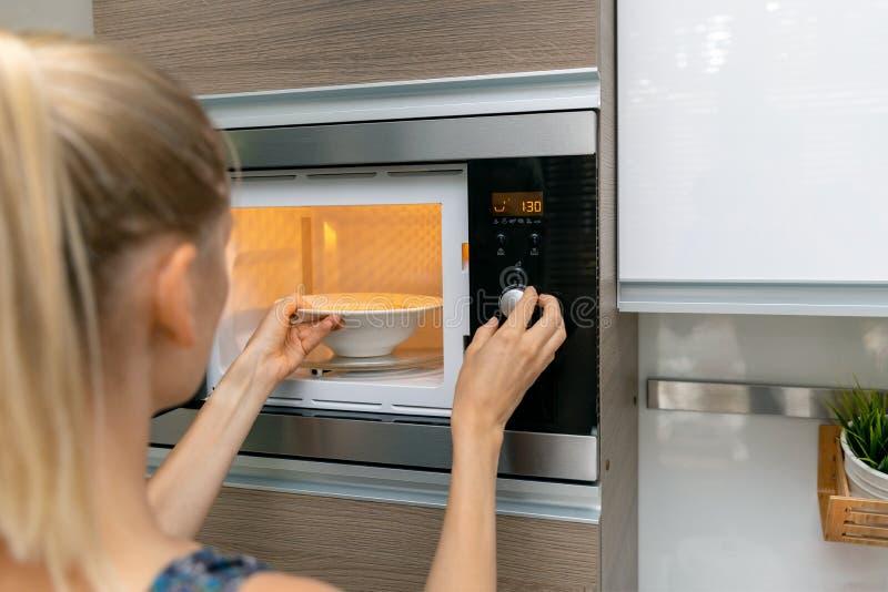 La donna si scalda l'alimento in forno a microonde a casa fotografie stock libere da diritti