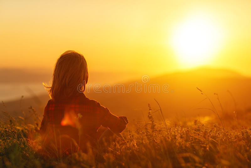 La donna si siede con lei indietro nel campo ed ammira il tramonto in montagne fotografie stock libere da diritti