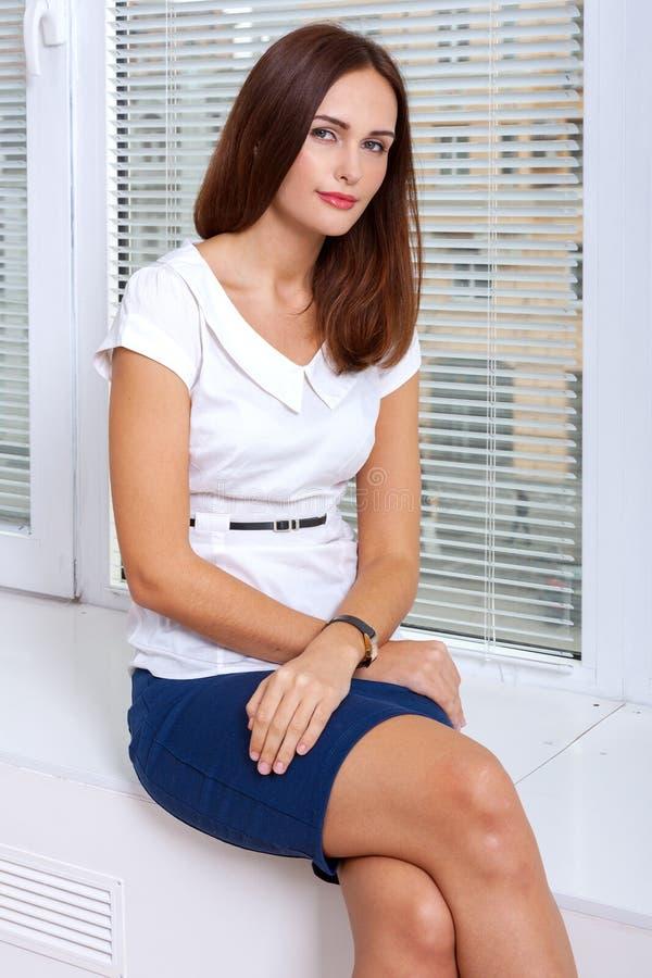 La donna si siede su un davanzale che mette le sue mani sulle sue ginocchia immagini stock