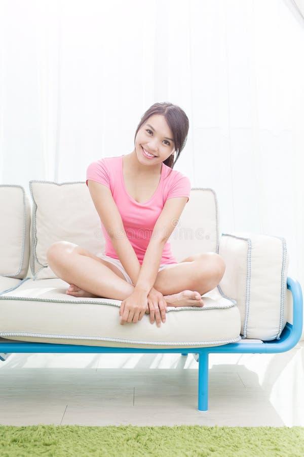 La donna si siede sul sofà immagini stock