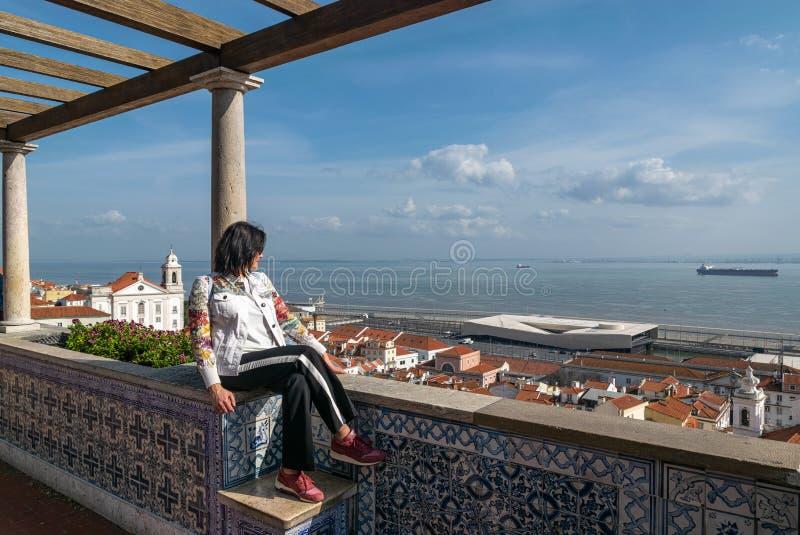 La donna si siede sulla piattaforma e sugli sguardi di osservazione ai tetti della città, il mare, la nave, il cielo con le nuvol immagini stock libere da diritti