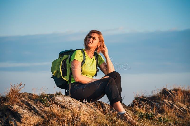 La donna si siede sulla scogliera ed esamina le cime fotografia stock