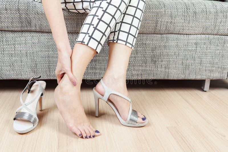 La donna si siede sulla sedia e la mano femminile con dolore del piede dopo, prende SH fotografia stock
